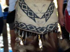 Los trajes rituales y tradicionales de las comunidades son trabajados con materiales del entorno, generalmente los trajes son realizados con cortezas de árbol Yanchama, tinta de Huito semillas y escamas de pirarucú. los símbolos que vemos en esta falda son un rostro felino y las pintas de una anaconda dos animales de gran impacto filosófico y espiritual para las comunidades.