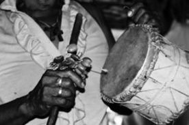 """Tambor Tikuna y sonajero, Los hombres elaboran tambores con pie curtida de venado, templada con fibra de chambira sobre una caja de resonancia de corteza de madera. Estos tambores son de uso ritual en la """"fiesta de pelazón"""" y luego pueden ser vendidos. Las mujeres hacen collares entretejiendo sobre una fibra de chambira plumas de colores, ala de insectos, semillas, caracoles y huesecillos de animales para su uso o para la venta."""